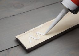 47527917 - putting glue on a piece of wooden baseboard